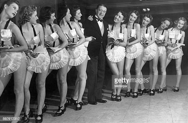 Comedian Tommy Handley stands with a line up of modern girl secretaries at Jack Hylton's new revue ITMA premier during the Second World War February...