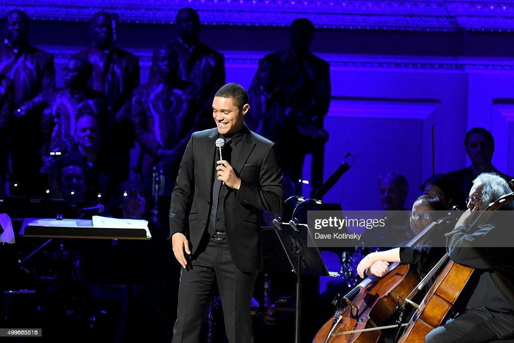 Comedian Trevor Noah speaks on stage during the ONE Campaign and (RED)'s concert to mark World AIDS Day, celebrate the incredible progress that's been made in the fights against extreme poverty and HIV/AIDS, and to honor the extraordinary leaders, dedicated activists, and passionate partners who have made that progress possible. At Carnegie Hall on December 1, 2015 in New York City.