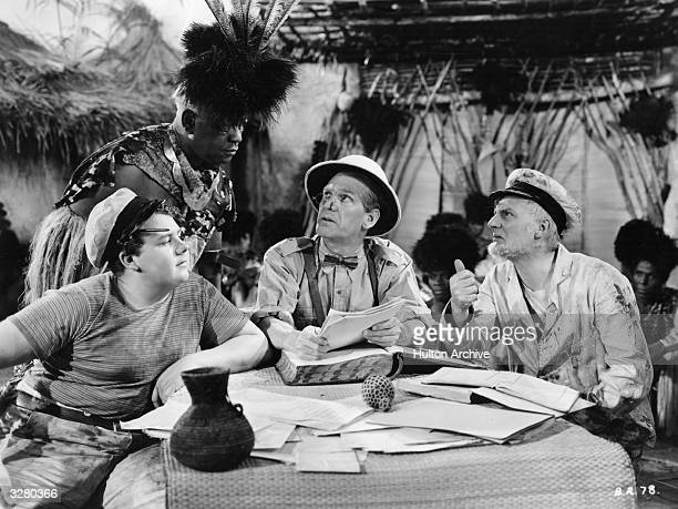 Comedian Will Hay centre discusses affairs with a native of his village in the company of Graham Moffatt left and Moore Marriott right in a scene...