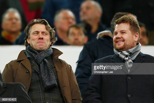 Comedians John Bishop and James Corden are seen on the stand prior to the Barclays Premier League match between West Ham United and Liverpool at...