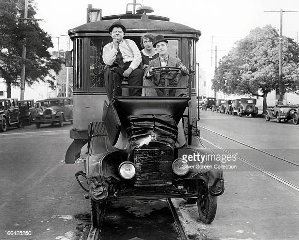 Comedians Oliver Hardy and Stan Laurel in their Model T Ford after it has been crushed by two trolley cars in a scene from the French language...