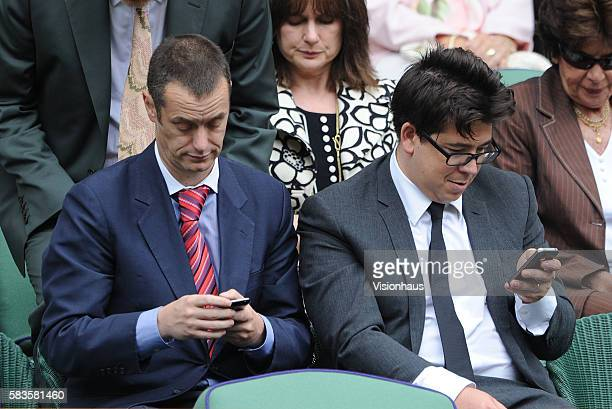 Comedians Paul Tonkinson and Michael McIntyre study their mobile phones during the Ladies Singles Final match between Serena Williams and Agnieszka...