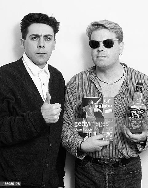 Comedians Sean Hughes and Eddie Izzard pose for a studio portrait London 1994 Izzard is holding a bottle of Jack Daniel's and a Crystal Palace FC...