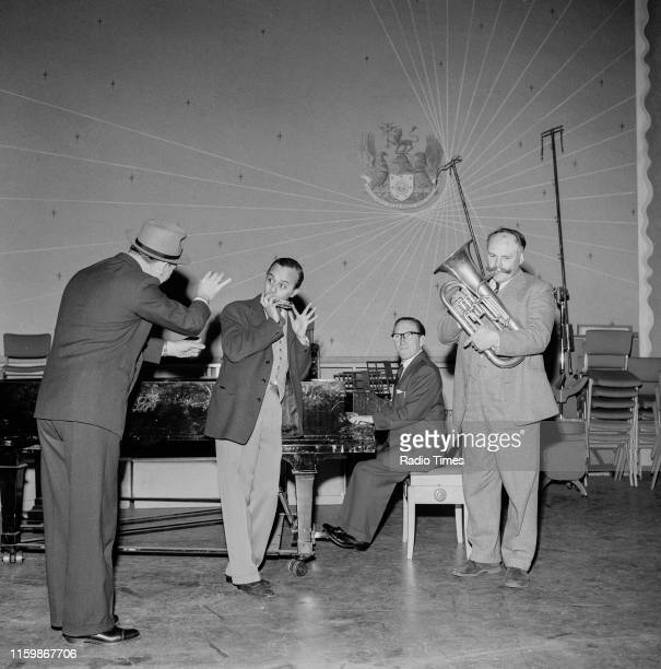 Comedians Tommy Trinder, Derek Roy, Arthur Askey and Jimmy Edwards joking around with musical instruments during a recording for the BBC Radio 4...