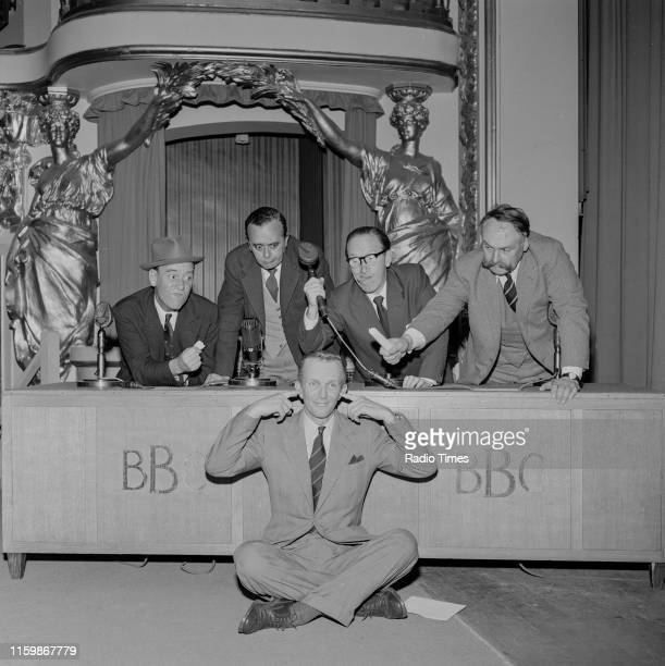 Comedians Tommy Trinder Derek Roy Arthur Askey and Jimmy Edwards joking around with BBC continuity announcer McDonald Hobley during a recording for...
