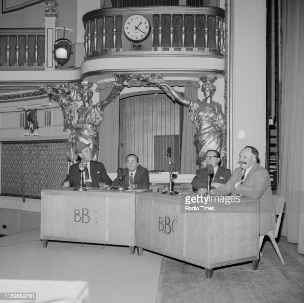 Comedians Tommy Trinder, Derek Roy, Arthur Askey and Jimmy Edwards sitting behind microphones during a recording for the BBC Radio 4 comedy series...