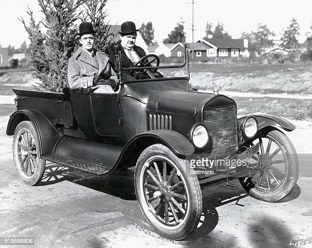 Comedic duo Laurel and Hardy sit in a Model T Ford with a Christmas tree on the set of Big Business