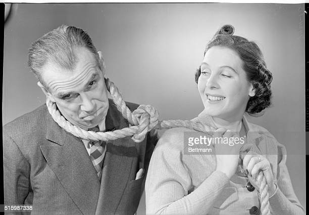 Comedic pose of smiling woman holding the end of a noose that is around a man's neck the man has a hangdog expression Ca 1940s