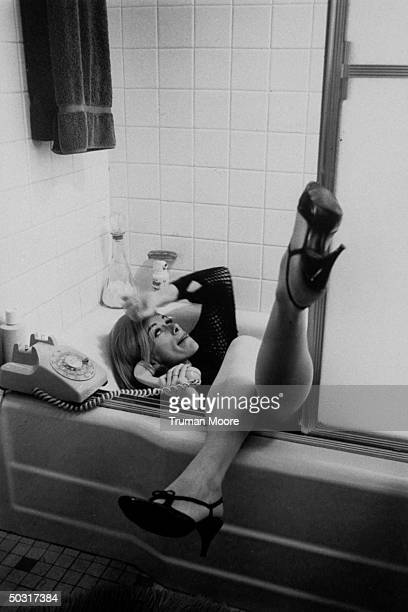 Comedienne Joan Rivers talking on the phone while lounging in a bathtub