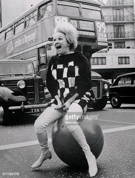 Comedienne Phyllis Diller laughs it up as she sits on a big ball in the middle of the street She was here to a television show and then vacation in...