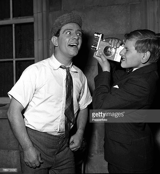 Comedy actor Norman Wisdom being filmed close up by boy actor Michael Caridea on the set of the film 'Up In The World' at Pinewood Studios 1956
