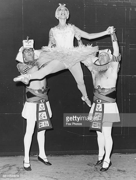 Comedy double act Eric Morecambe And Ernie Wise holding ballet dancer April Olrich in the air filming a scene from 'The Intelligence Men' at Pinewood...