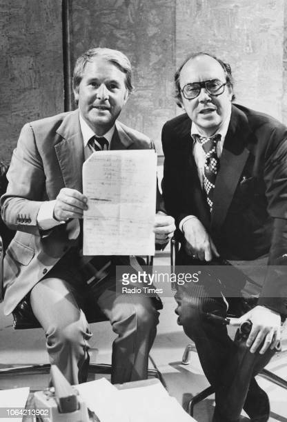 Comedy double act Eric Morecambe and Ernie Wise holding up a handwritten note on the set of the television show 'It's Childsplay' June 10th 1976