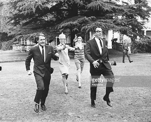 Comedy double act Ernie Wise and Eric Morecambe running through a garden followed by actresses April Olrich and Jacqueline Jones filming scenes for...
