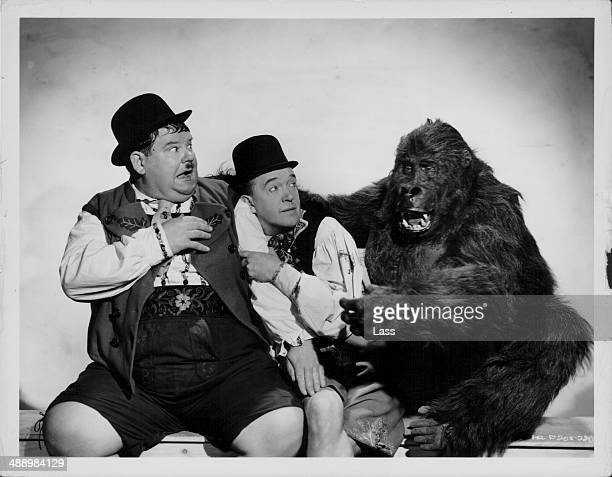 Comedy double act Oliver Hardy and Stan Laurel posing with a man in a gorilla suit in a promotional portrait for the movie 'Swiss Miss' 1938