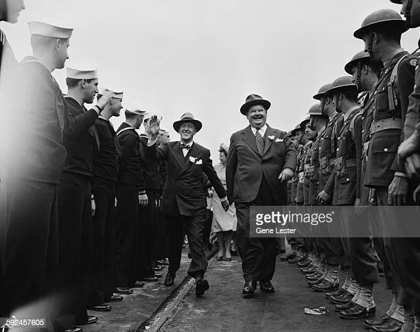 Comedy duo Stan Laurel and Oliver Hardy laugh and smiles as they walk along a line of soldiers and sailors late 1930s or early 1940s