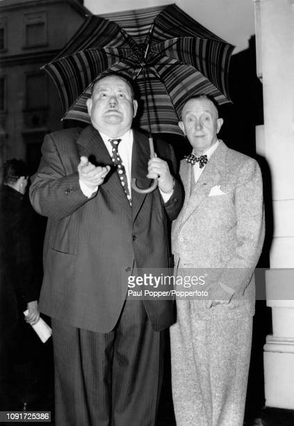 Comedy duo Stan Laurel on right and Oliver Hardy pictured together sheltering from the rain under an umbrella outside their hotel in London following...