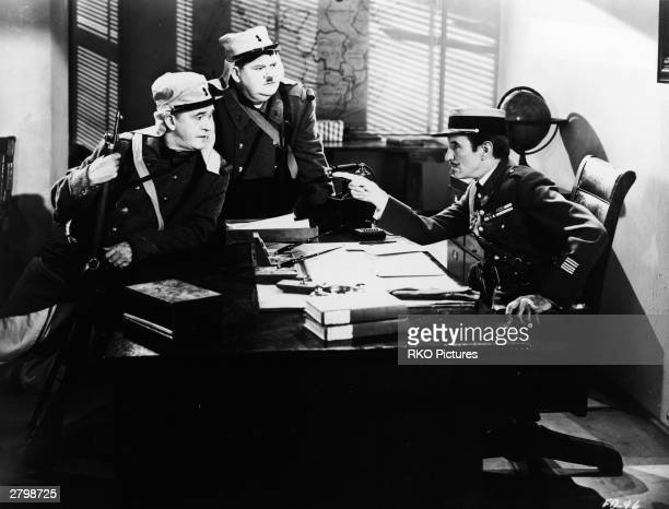 Comedy team Stan Laurel and Oliver Hardy stand in costume as Foreign Legionaires as actor Charles Middleton points to them in a still from the film...