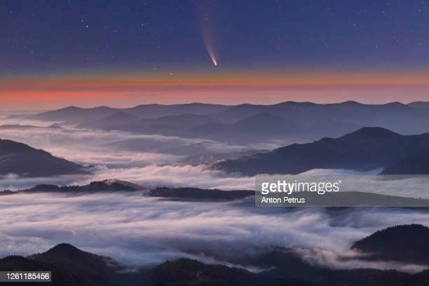 comet neowise c/2020 f3 at sunet over misty mountains - orbiting stock-fotos und bilder