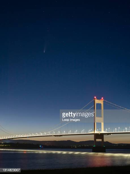 Comet Neowise over the Severn Bridge between England and Wales at twilight in July 2020 viewed from the bank of the River Severn.