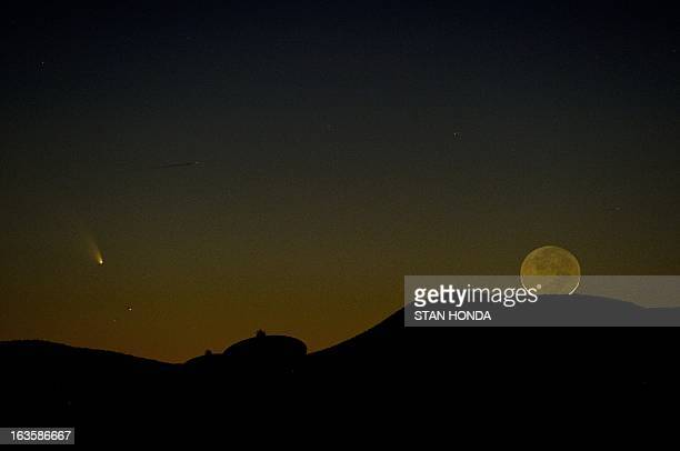 Comet PanSTARRS is seen with a one-day old crescent moon as both set over the Very Large Array radio telescope antenna dishes March 12, 2013 near...