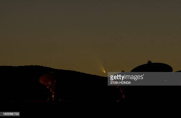 Comet PanSTARRS sets over the Very Large Array radio telescope antenna dishes March 12, 2013 near Magdalena, New Mexico. The comet, now just faintly...