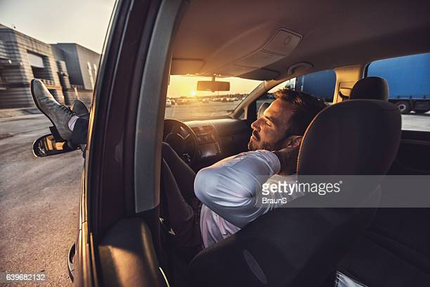 Comfortable businessman taking a nap in the car.