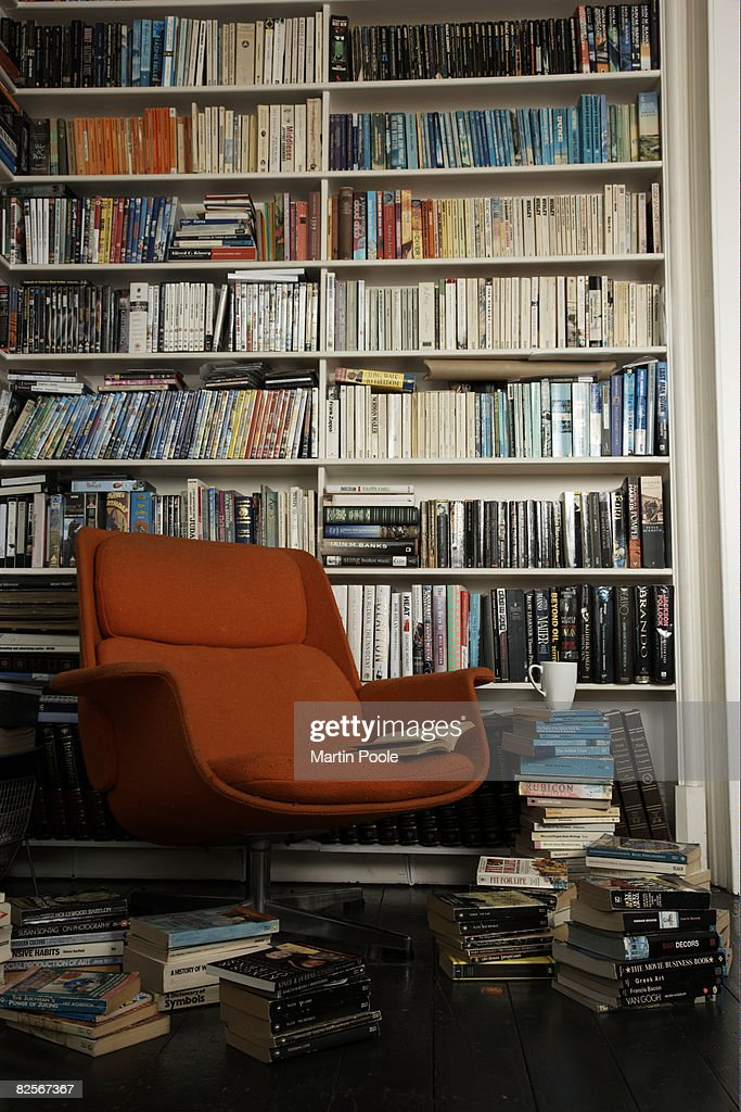 comfortable chair surrounded by books : Stock Photo