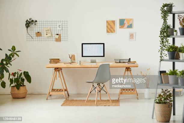comfortable workplace with potted plants, wall organizer, pictures and computer - home office stock pictures, royalty-free photos & images
