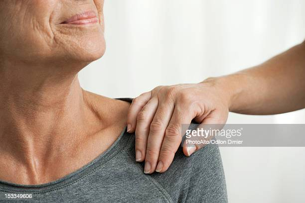 comforting hand on senior woman's shoulder, cropped - hand on shoulder stock pictures, royalty-free photos & images