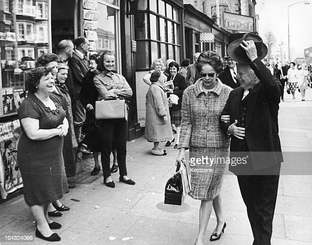 Comic actor Charlie Chaplin acknowledging his welcome during a walk with his wife Oona O'Neill on the Old Kent Road near his birthplace in Southwark...