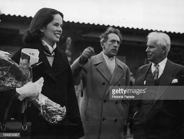 Comic actor Charlie Chaplin and his wife Oona O'Neill are met at Nice Airport, France by French writer and filmmaker Jean Cocteau , 8th March 1953.