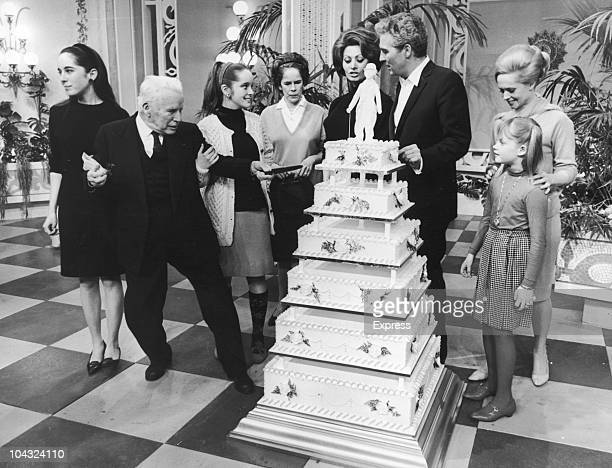 Comic actor Charlie Chaplin attacks a seventiered cake on his 77th birthday at Pinewood Studios Buckinghamshire 16th April 1966 With him are his wife...