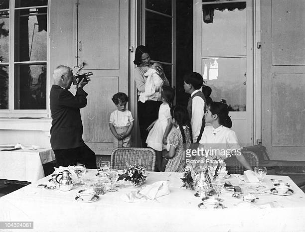 Comic actor Charlie Chaplin films his wife Oona O'Neill as she holds their newborn daughter Jane at their home the Manoir de Ban Switzerland May 1957...