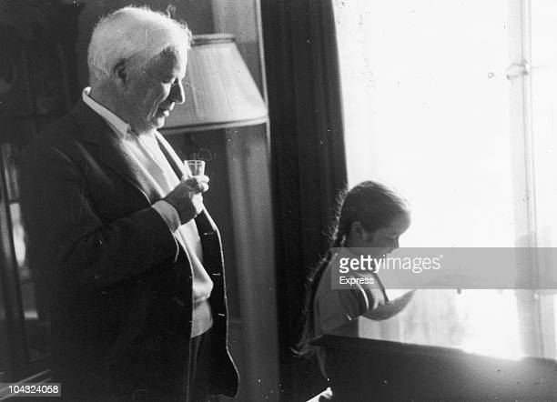 Comic actor Charlie Chaplin looks on as his daughter Victoria plays a piano sonatina to celebrate his 71st birthday 19th April 1960