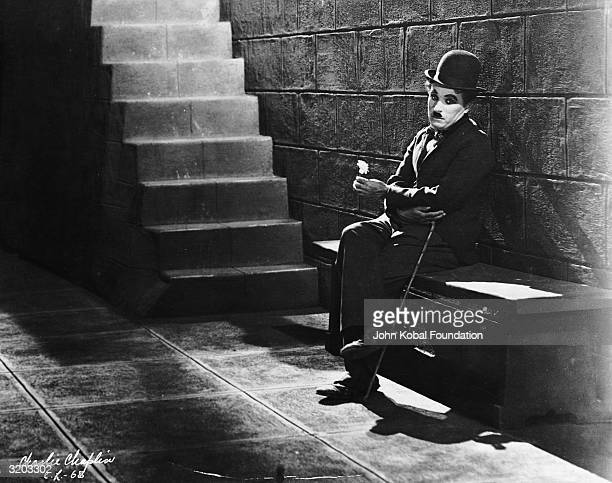 Comic actor Charlie Chaplin sitting forlornly at the bottom of the steps in a scene from the film 'City Lights'