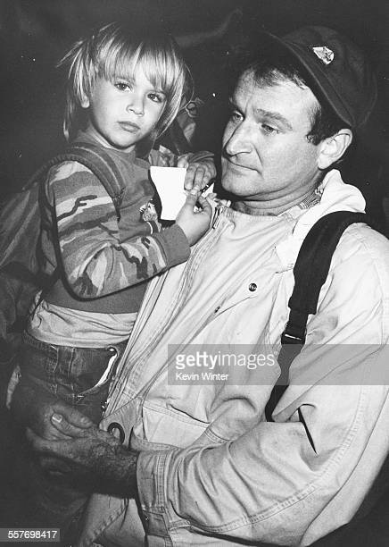 Comic actor Robin Williams holding his young son Zachary leaving Universal Amphitheatre after recording 'Comic Relief '87' in Los Angeles, November...