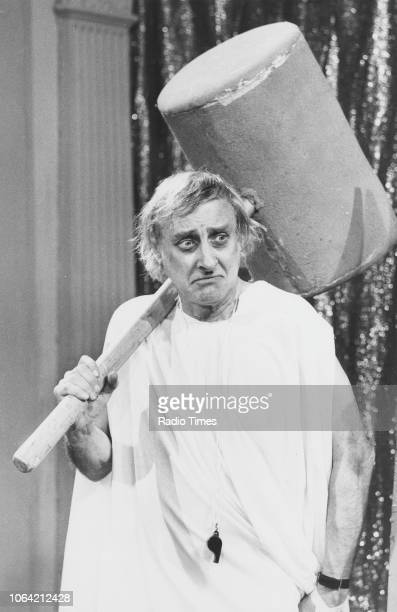 Comic actor Spike Milligan carrying an oversized mallet in a sketch from the television show 'There's a Lot of It About' May 12th 1982
