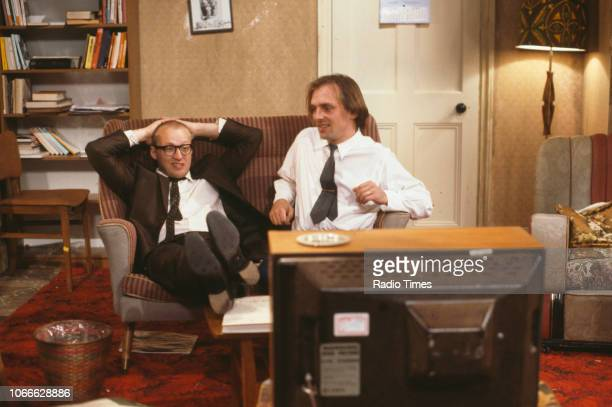 Comic actors Adrian Edmondson and Rik Mayall watching television in scene from episode 'Contest' of the BBC television sitcom 'Bottom', June 24th...