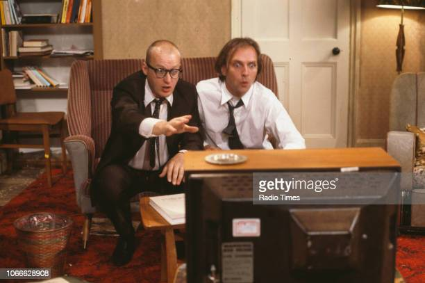 Comic actors Adrian Edmondson and Rik Mayall watching television in scene from episode 'Contest' of the BBC television sitcom 'Bottom' June 24th 1990
