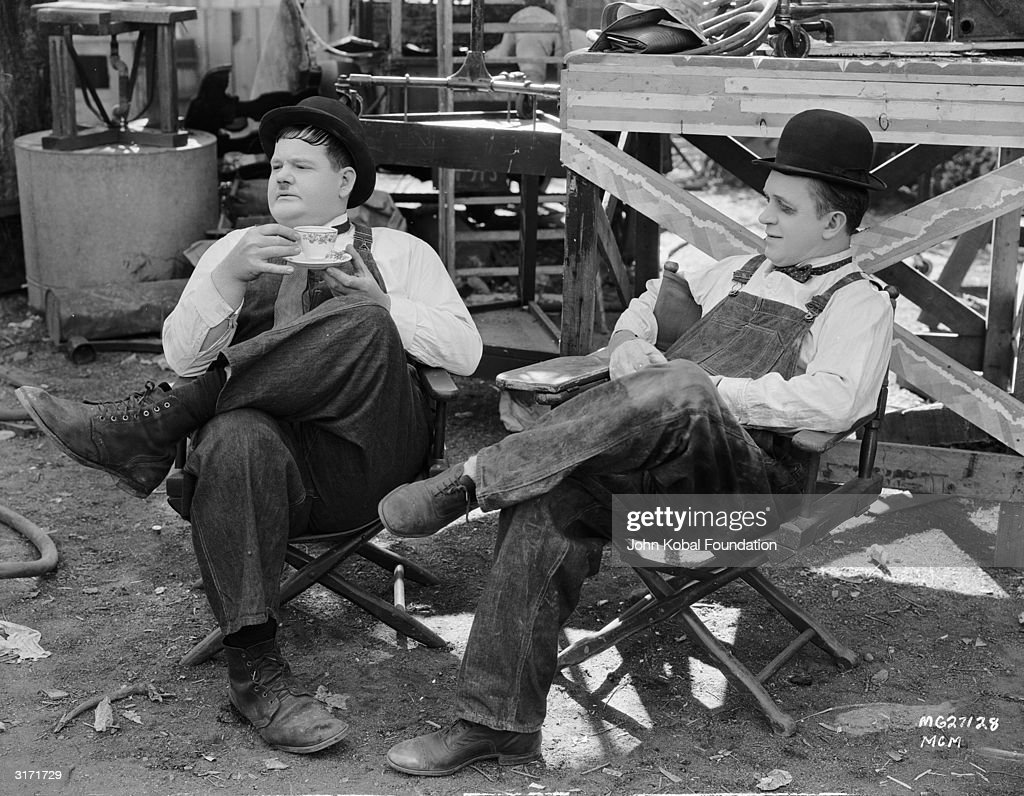 Comic actors Oliver Hardy (1892 - 1957, left) and Stan Laurel (1890 - 1965) during a break in the filming of 'Towed In A Hole', directed by George Marshall, 1932.