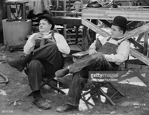Comic actors Oliver Hardy and Stan Laurel during a break in the filming of 'Towed In A Hole' directed by George Marshall 1932