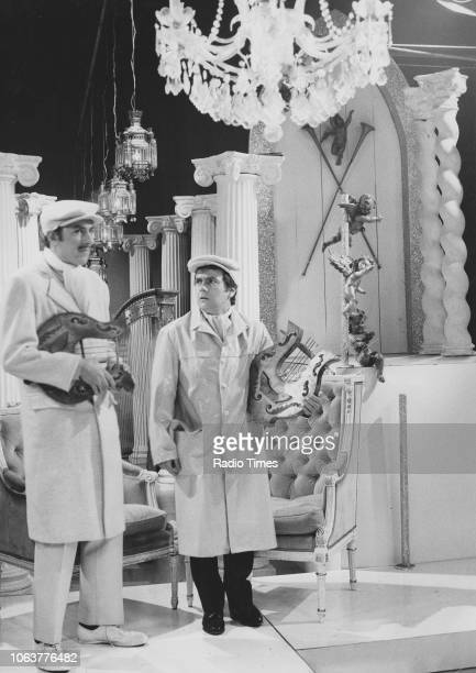 Comic actors Peter Cook and Dudley Moore wearing flat caps and overalls in a scene from the television show 'Not Only But Also' February 20th 1966