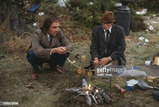 Comic actors Rik Mayall and Adrian Edmondson sitting around a campfire on Wimbledon Common in a scene from episode 'S Out' of the BBC television...
