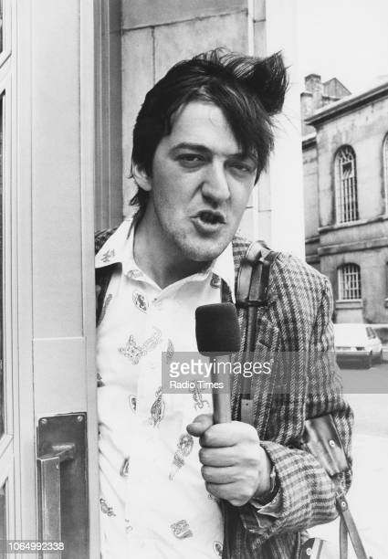 Comic actors Stephen Fry holding a portable microphone, photographed for Radio Times in connection with the BBC Radio 4 series 'Delve Special', July...
