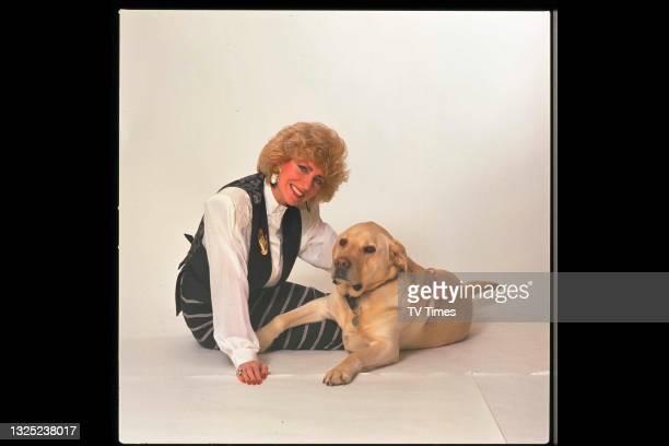 Comic actress and impressionist Faith Brown photographed with a Labrador Retriever, circa 1990.