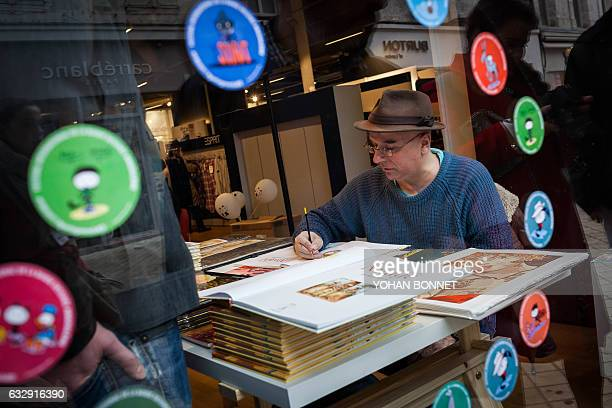 A comic book artist signs autographs during the 44th international comic book festival on January 28 2017 in Angouleme / AFP / Yohan BONNET