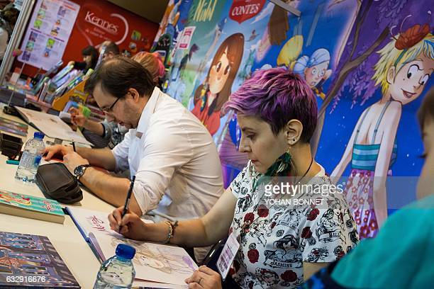 Comic book artists sign autographs during the 44th international comic book festival on January 28 2017 in Angouleme / AFP / Yohan BONNET