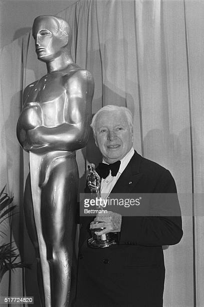 Comic Charlie Chaplin stands by an Oscar statue after the 44th Annual Academy Awards presentation at the Music Center Chaplin returned to the United...