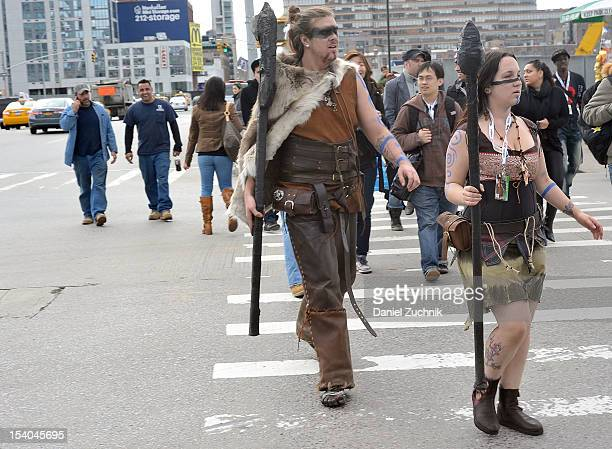 Comic Con attendees wearing cavemen costumes walk to the 2012 New York Comic Con at the Javits Center on October 12 2012 in New York City